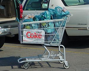 A shopping cart filled with bagged groceries l...