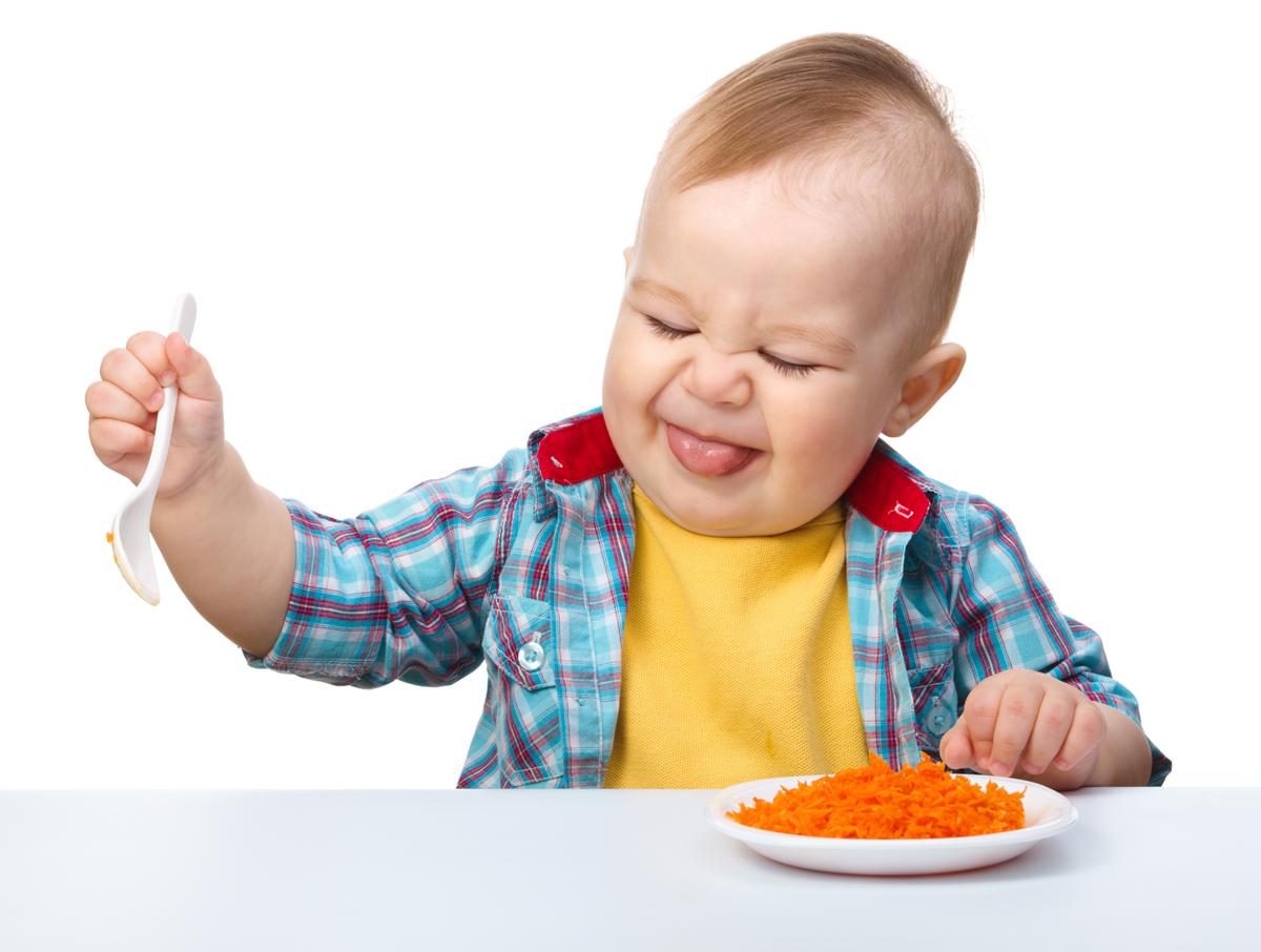 Little boy refuses to eat making unpleasant grimace, isolated over white