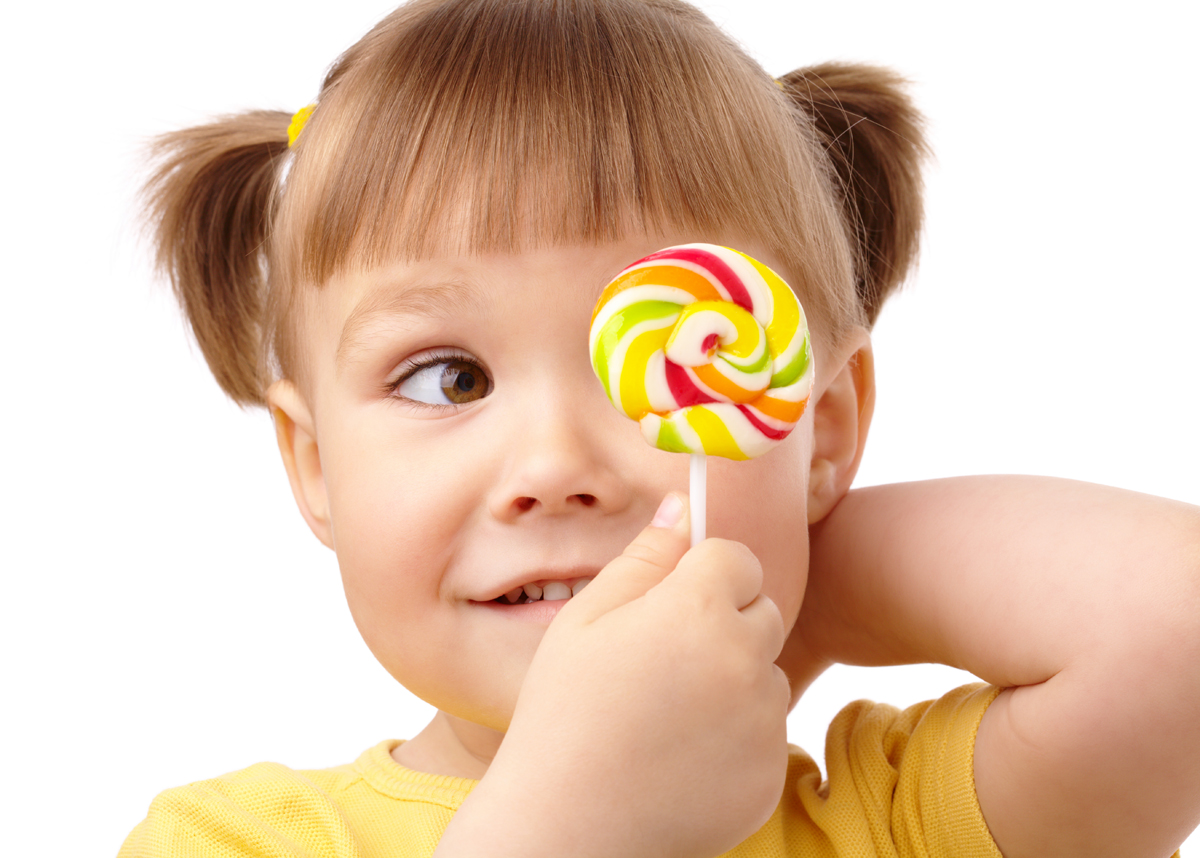 Cute little girl is looking at her colorful lollipop, isolated over white