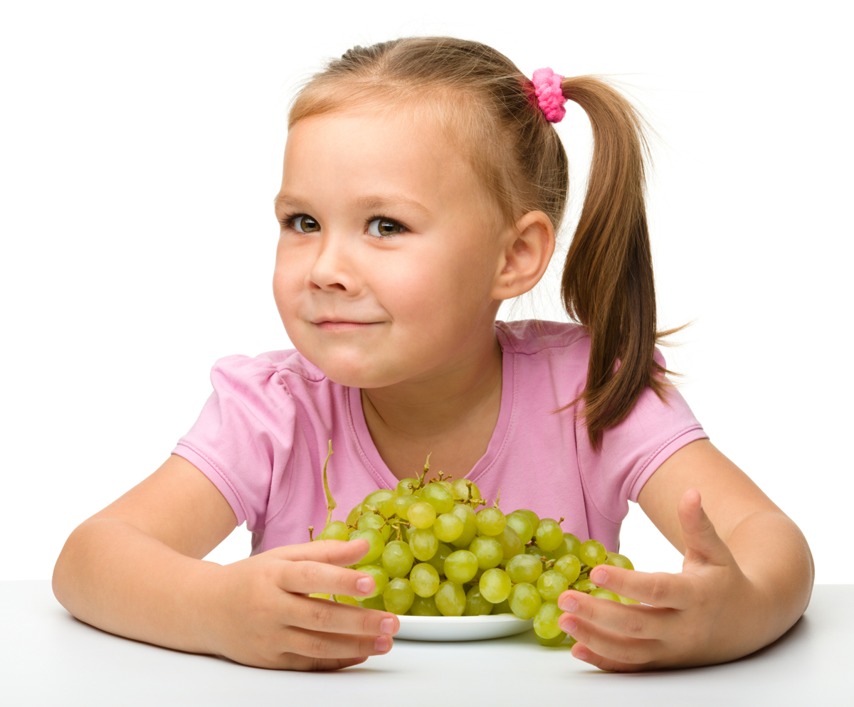 Little girl is eating grapes, isolated over white