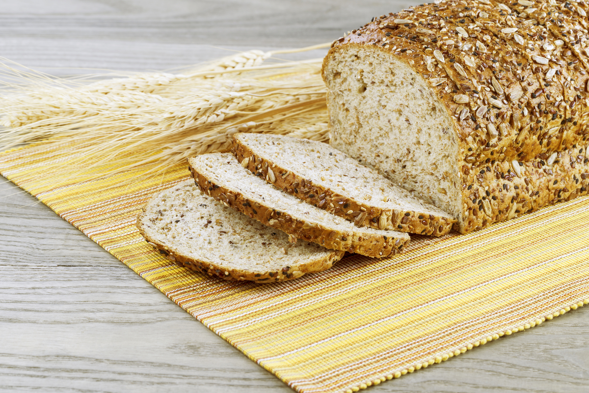 Fresh sliced whole bread with wheat stalks, yellow cloth place mat on faded wooden table