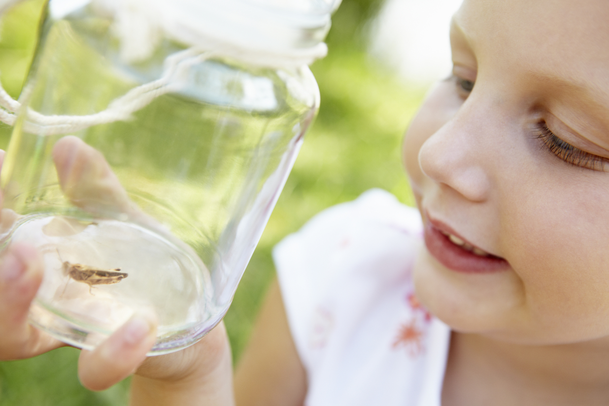 Little girl with cricket in a jar