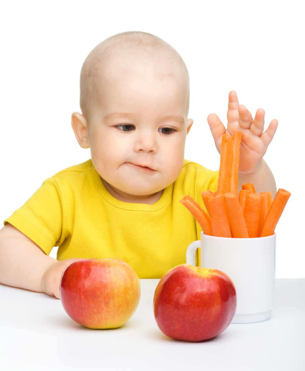 Little boy pulling up carrot from a cup, isolated over white
