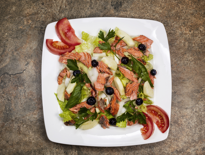 Red Salmon Salad with fresh garden tomatoes, basil, parsley, lettuce, onion, pears on white plate