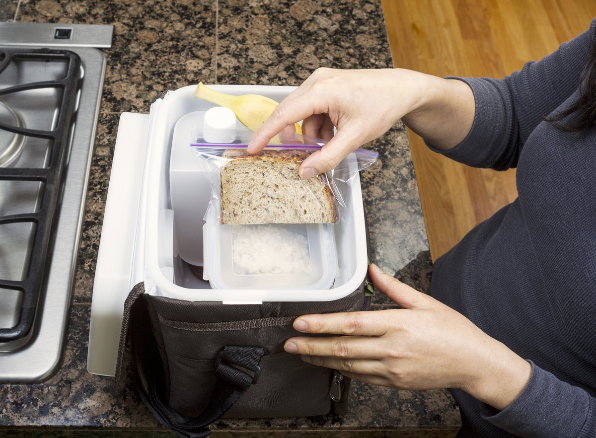 Female hands packing lunch into portable bag while in the kitchen on stone counter top next to stove