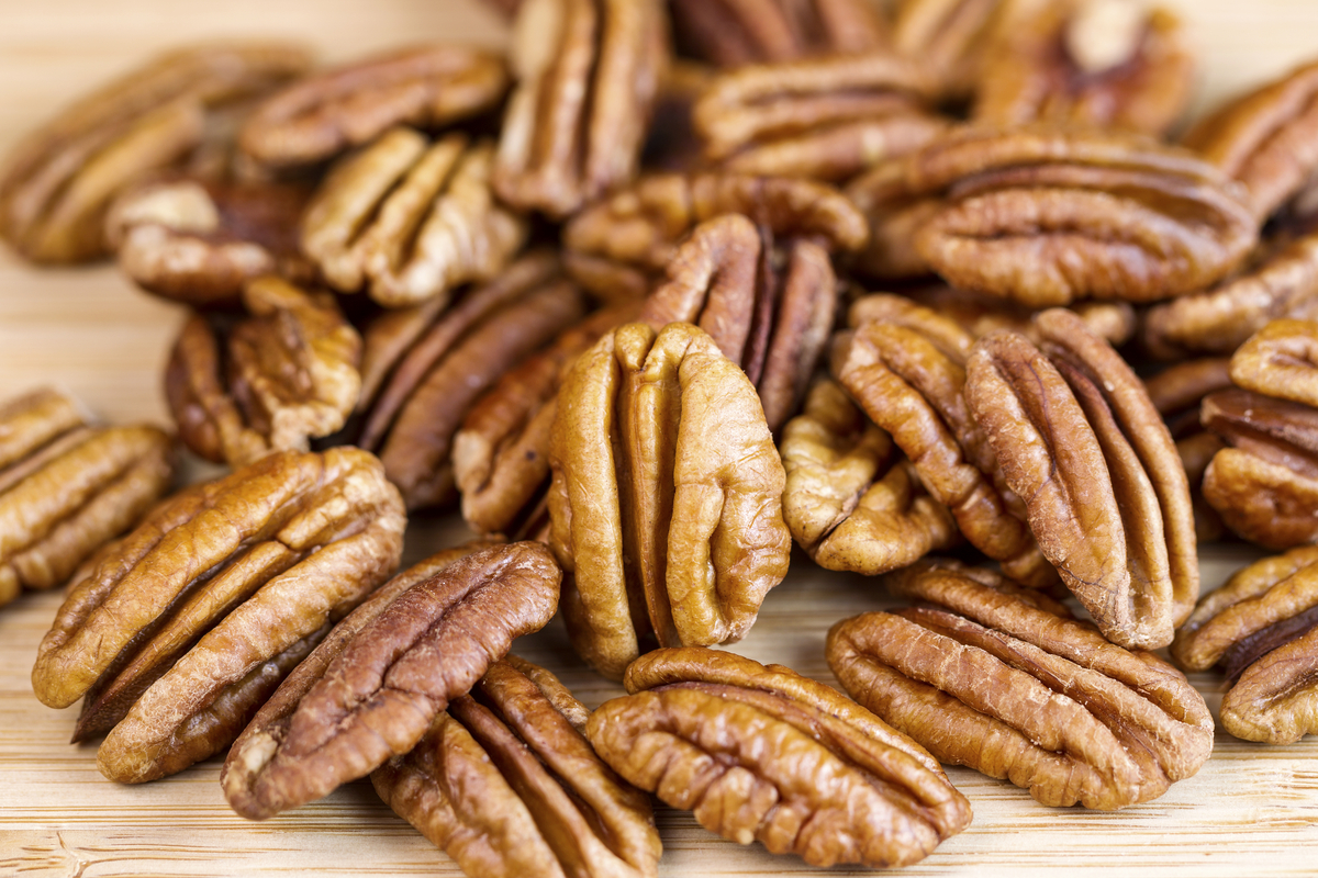 Horizontal photo of slightly roasted pecan nuts with focus of standing pecan in front of pile on natural wood
