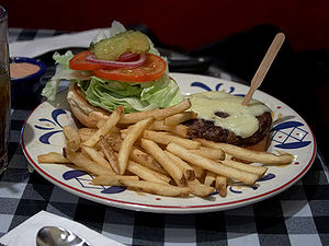 Hamburger and fries served in an American dinn...
