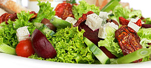 A garden salad with lettuce, sundried tomatoes...