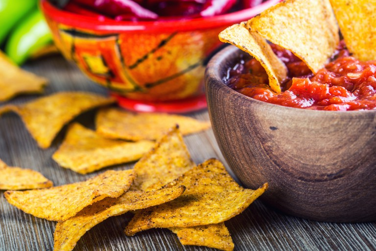 Salsa with tortilla chips and chilli peppers.Concept