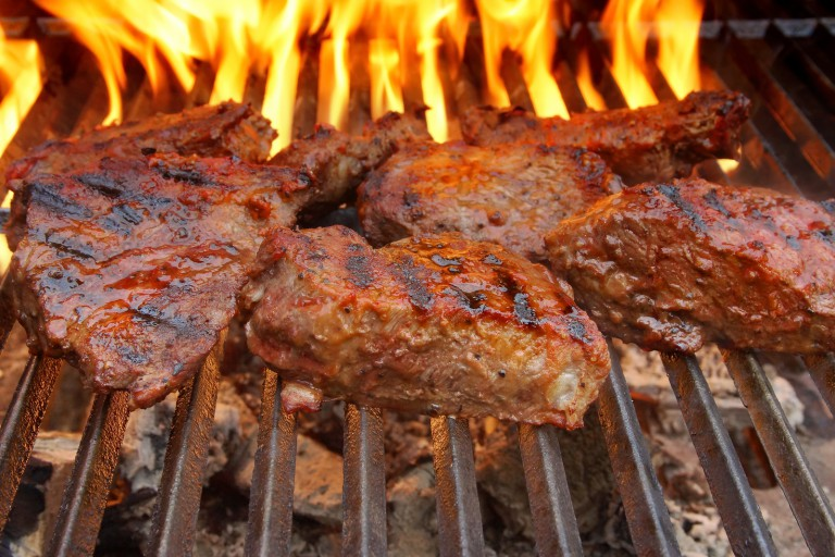 Beef Steak On The Bbq Grill With Flames.