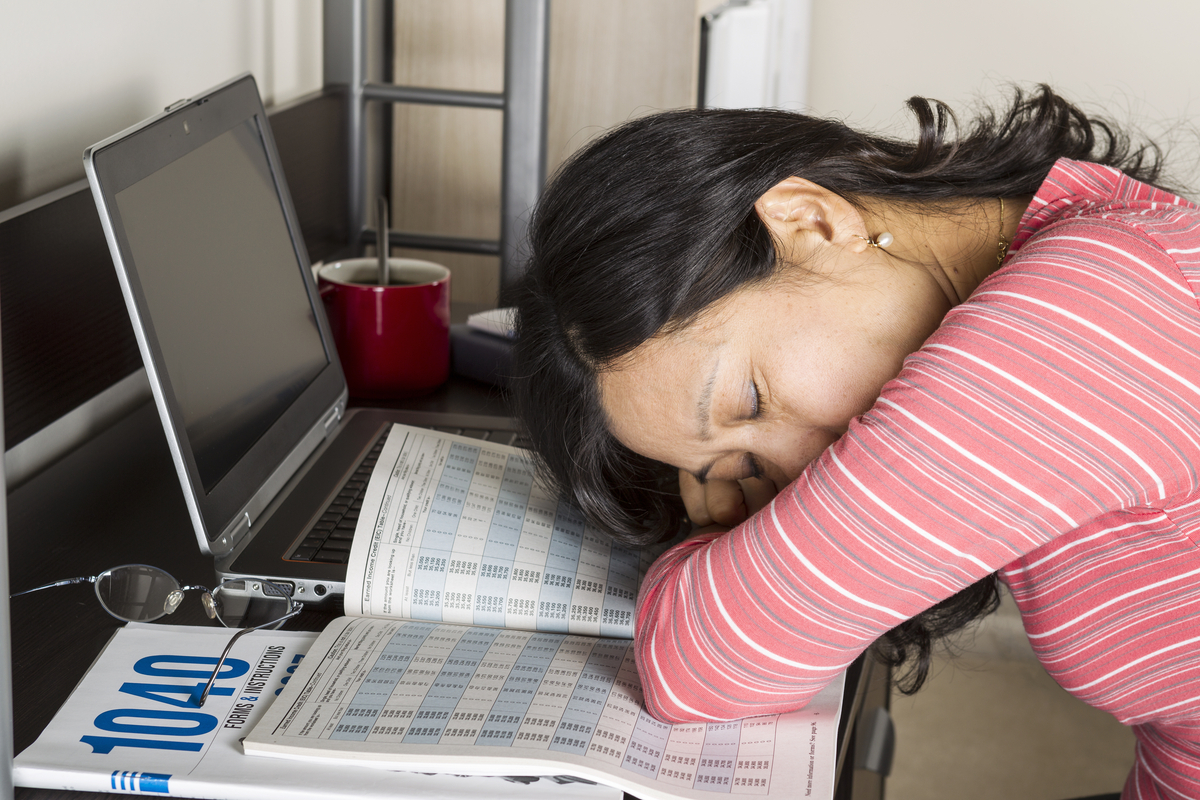 Mature Asian woman with head down on income tax tables booklet with computer, coffee  cup and glasses on desk
