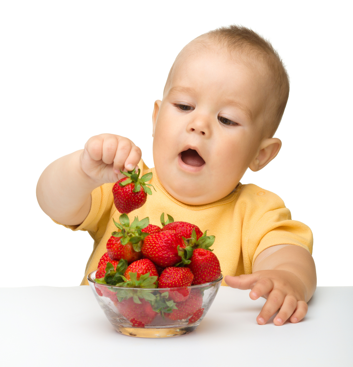 Happy little boy with strawberries, isolated over white